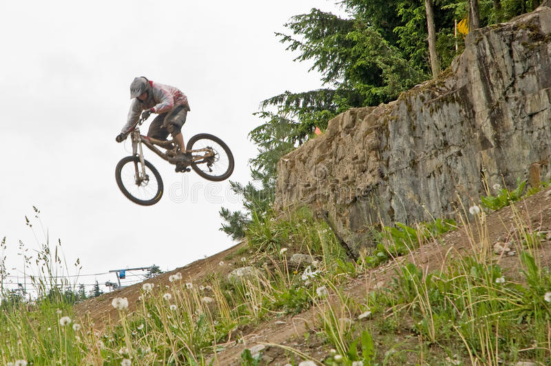 Mountain bike jumping. A view of a rider on a mountain bike, flying through the air over a jump stock photo