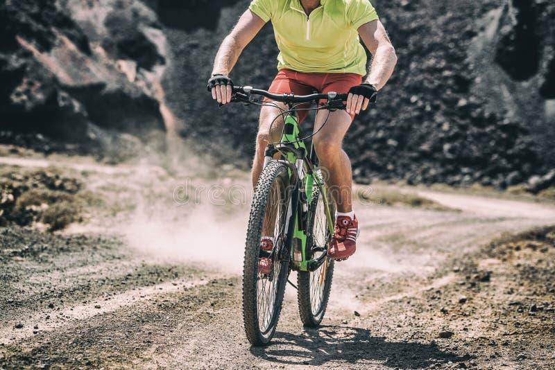 Mountain bike MTB biking athlete man in mountains landscape jumping riding bicycle. Professional bicycle rider body crop training stock photography