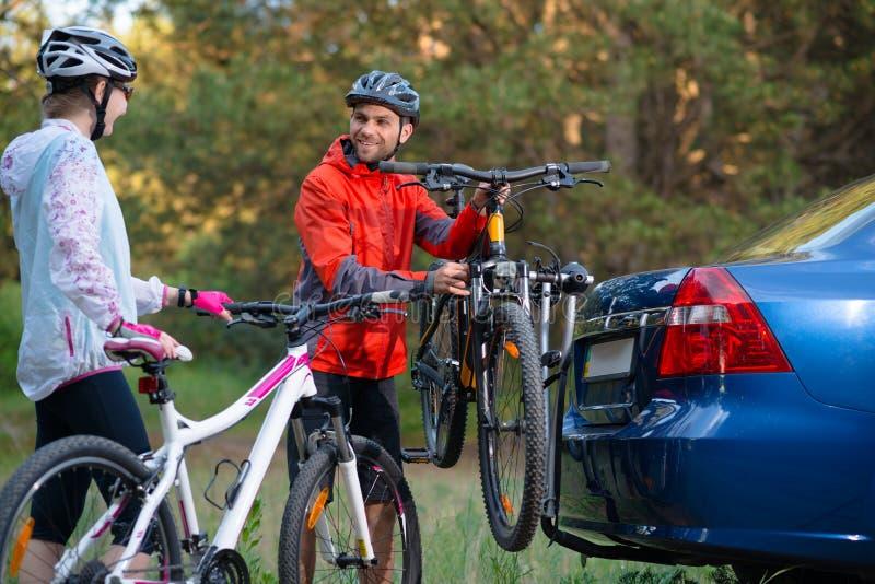 Mountain bike novos de Unmounting dos pares da cremalheira da bicicleta no carro Conceito do curso da aventura e da família imagens de stock royalty free