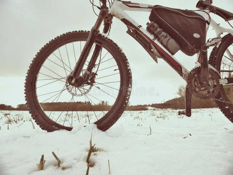 Mountain bike in powder snow. Lost path in snowdrift. Wheel detail. Mountain bike stay in powder snow. Lost path in snowdrift. Wheel detail. Snow flakes melting stock photo