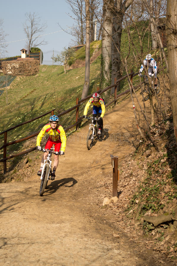 Mountain bike race. Cyclists rides down a path among the trees during a mountain bike competition over the mount Canto (Bergamo, Italy royalty free stock image