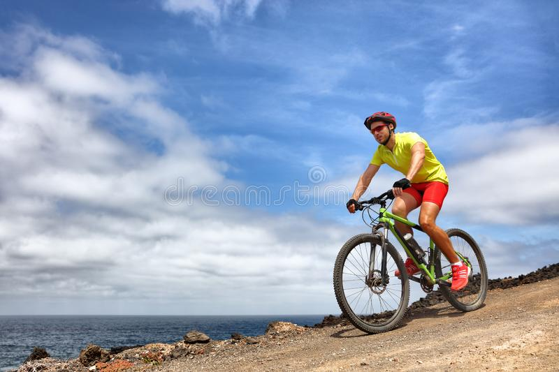 Mountain bike sport man riding MTB bicycle. Biking fitness athlete cyclist on mountain trail in summer outdoors. Sport health stock image