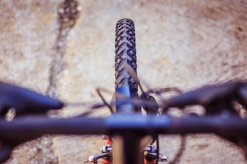 Mountain bike tyres outside, blurry handlebar, summer day, city mobility. Close up picture of a mountain bike tyre, blurry handlebar, summer day bicycle trip royalty free stock photos