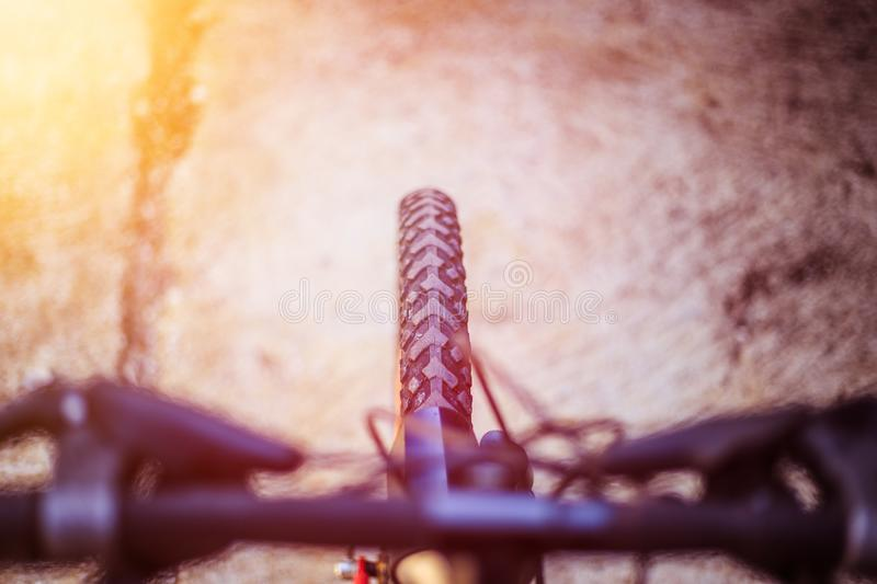 Mountain bike tyres outside, blurry handlebar, summer day, city mobility. Close up picture of a mountain bike tyre, blurry handlebar, summer day bicycle trip royalty free stock photo