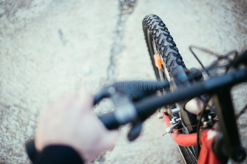 Mountain bike tyres outside, blurry handlebar, summer day, city mobility. Close up picture of a mountain bike tyre, blurry handlebar, summer day bicycle trip royalty free stock photography