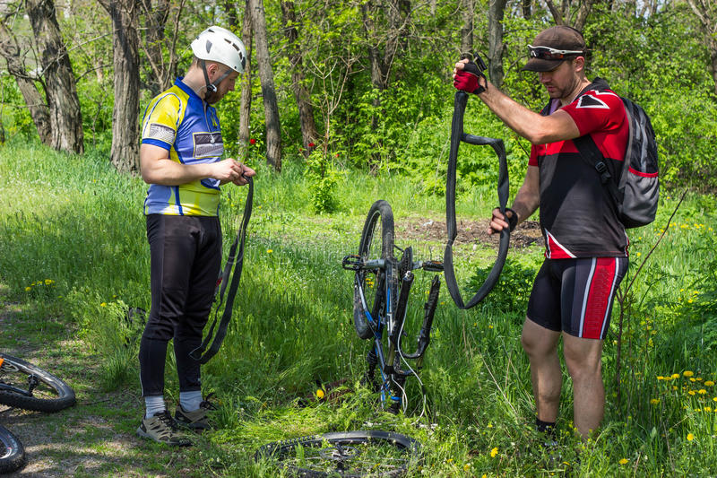 Mountain bike. Young people are repairing tire mountain bike stock images