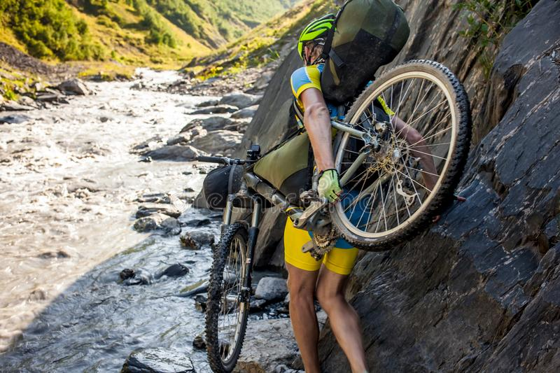 Mountain biker is crossing the river in the highlands of Tusheti region, Georgia.  royalty free stock images