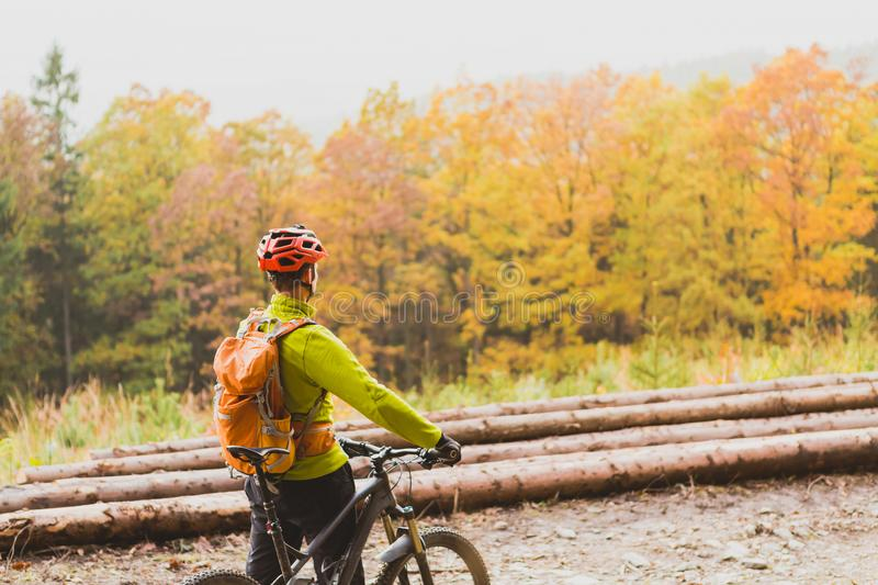 Mountain biker looking at inspiring forest landscape. Mountain biker looking at inspiring mountain landscape, standing with bicycle. Man cycling MTB on dirty stock image