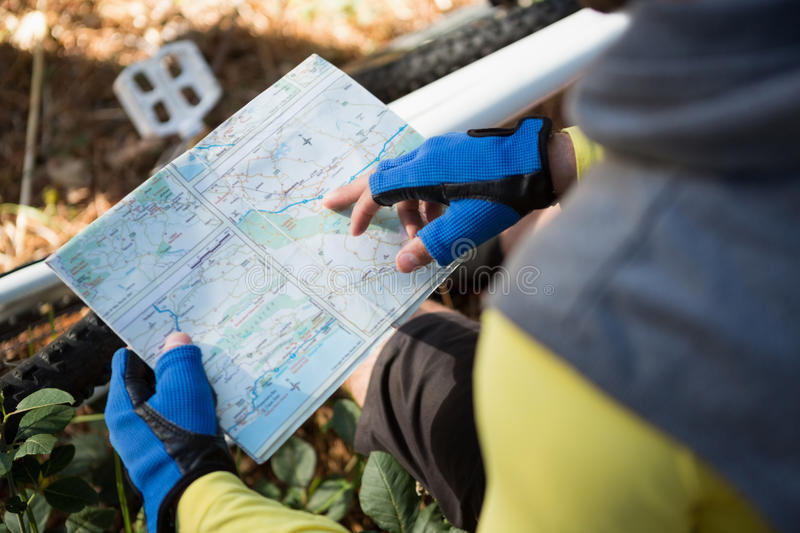 Mountain biker looking at map. In the forest royalty free stock photography