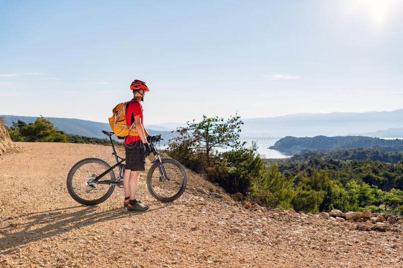 Mountain biker looking at the sea view. Mountain biker looking at view and riding on bike at the sea and summer mountains. Man rider cycling MTB on country road royalty free stock photography