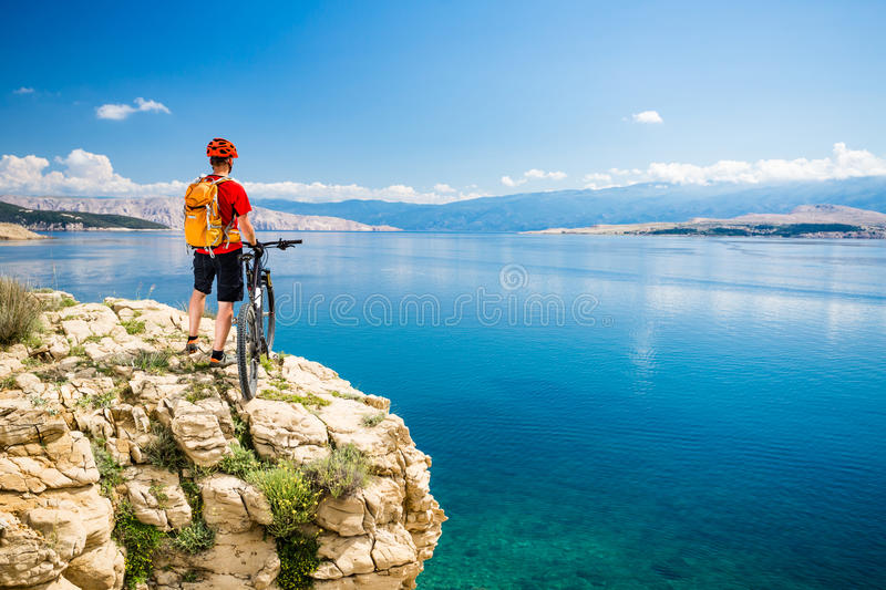 Mountain biker looking at view and riding on bike. Mountain biker looking at view and traveling on bike in summer sea landscape. Man rider cycling MTB on country royalty free stock photos