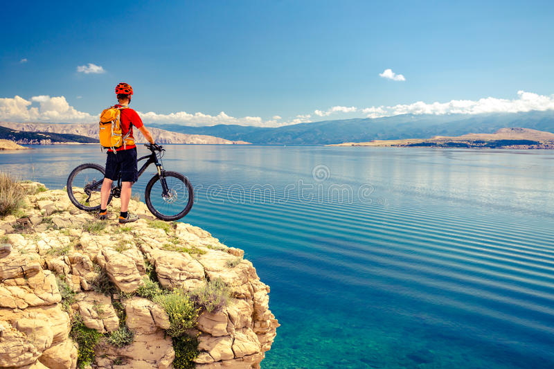 Mountain biker looking at view and riding a bike. Mountain biker looking at view and traveling on bike in summer sea landscape. Man rider cycling MTB on rocky stock images