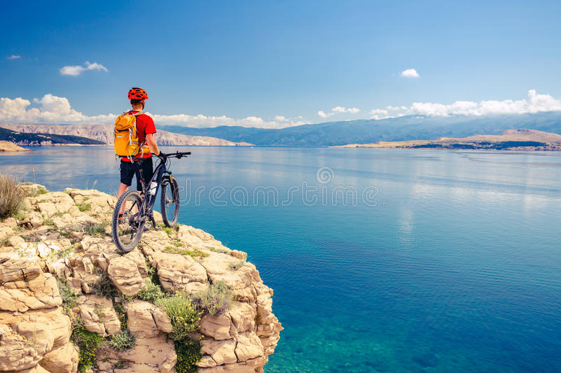 Mountain biker looking at view and riding a bike. Mountain biker looking at view and traveling on bike in summer sea landscape. Man rider cycling MTB on rocky royalty free stock photos