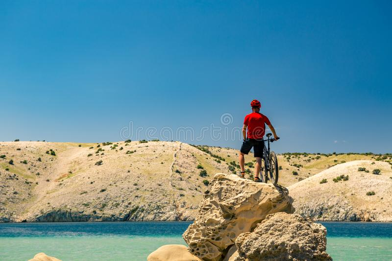 Mountain biker looking at mountains and beach stock images