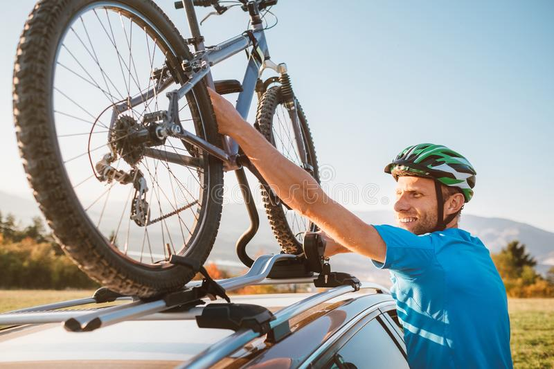 Mountain biker man take of his bike from the car roof royalty free stock photography