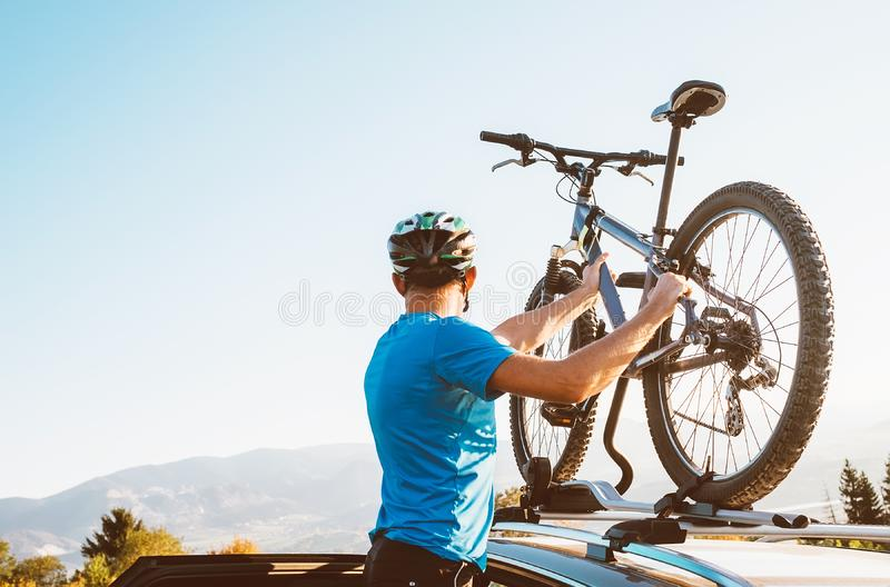 Mountain biker man take of his bike from the car roof royalty free stock image