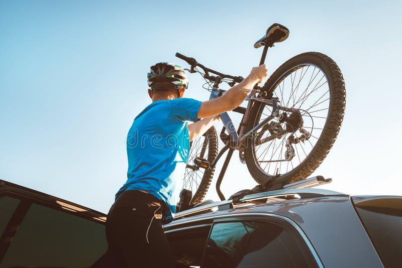 Mountain biker man take of his bike fron the car roof royalty free stock image