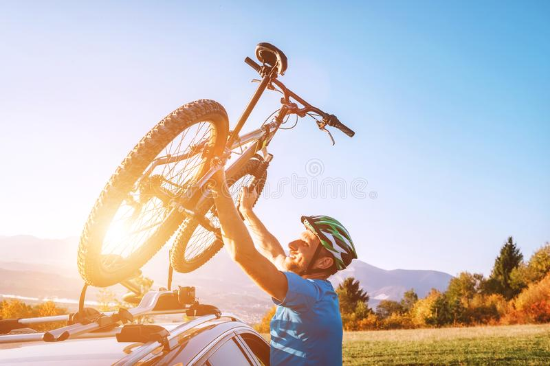 Mountain biker man take of his bike fronm the car roof. Active sport people concept image stock photos