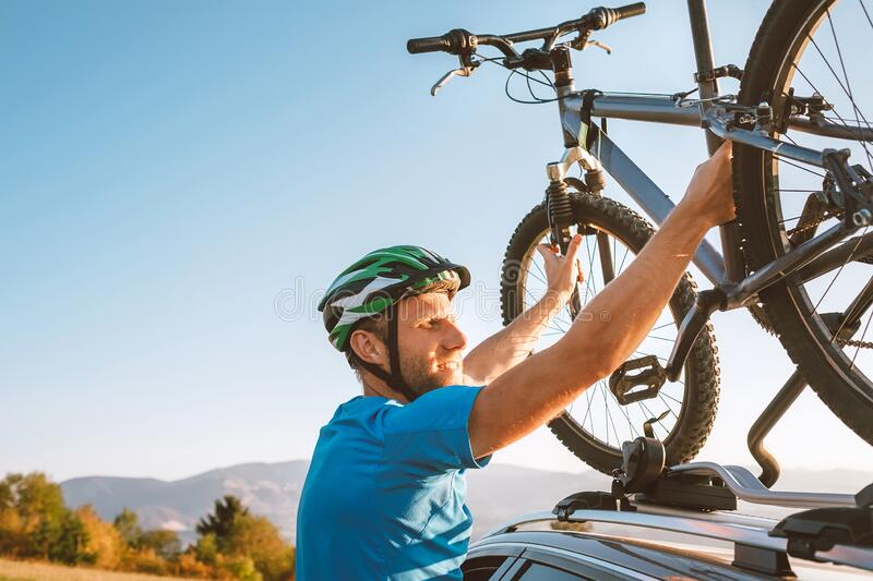 Mountain biker man take of his bike fronm the car roof. Active sport people concept image stock image