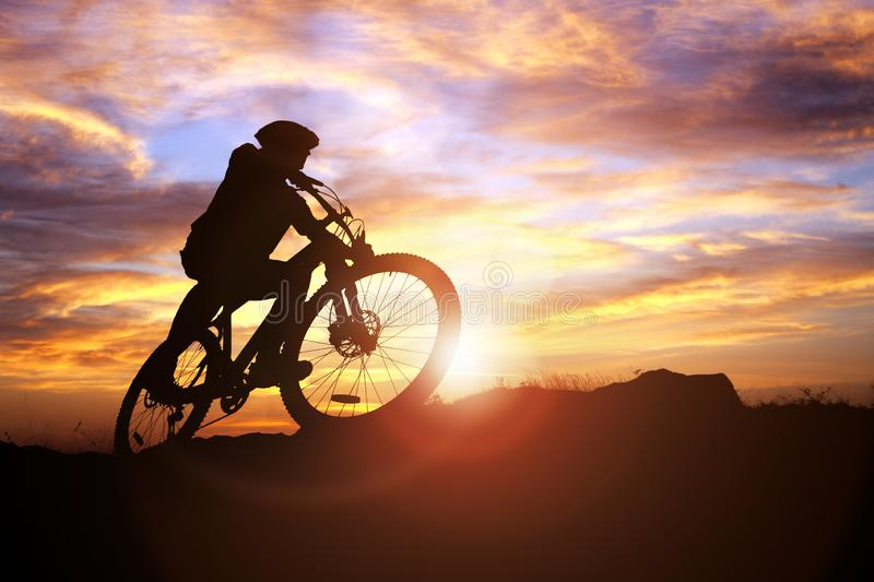 Mountain biker silhouette in action against the sunset concept f. Mountain biker silhouette against the sunset concept for achievement, conquering adversity and royalty free stock images