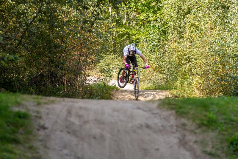 Mountain biker speeding downhill on a mountain bike track in the woods stock photography