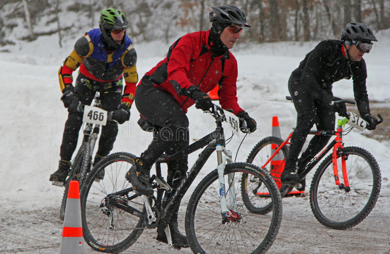 Mountain Bikers competing in winter race royalty free stock image