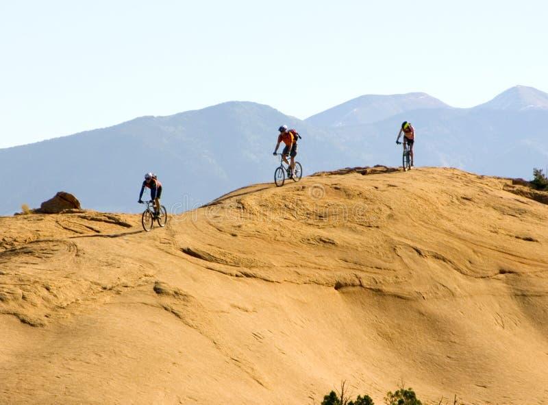 Mountain biking in the mountains. Mountain bikers climb rugged slickrock in Moab, Utah royalty free stock image