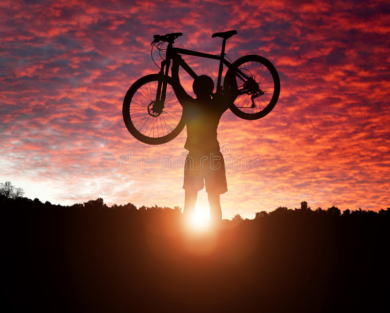 Mountain biking at sunset. Mountain biker silhouette against the sunset concept for achievement, conquering adversity and exercising stock photo