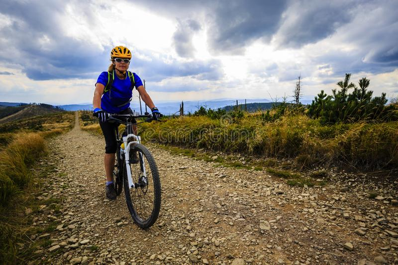 Mountain biking women riding on bike in summer mountains forest royalty free stock photo