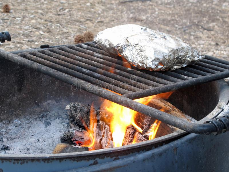 Mountain Camp Fire Cooking Foil Dinners on Grate Over Hot Pit. Camp Fire Cooking Foil Dinner Meals on Grate Red Over Hot Barbecue Pit during Summer stock photography