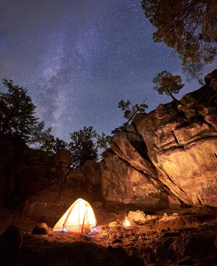 Mountain campsite at night amid huge steep rock formation. Tourist tent lit by burning campfire royalty free stock images
