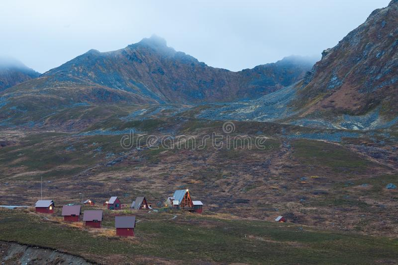 Mountain Chalets in Alaska. A cluster of homes in a town in Alaska, high in the mountains. It is morning, and fog can be seen on the tops of the hills royalty free stock photo