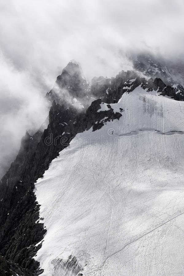 Mountain in Chamonix  in a bad weather with climbers. Two climbers trying to ascend the summit in bad weather conditions. Mountains covered by snow and ice with stock photo