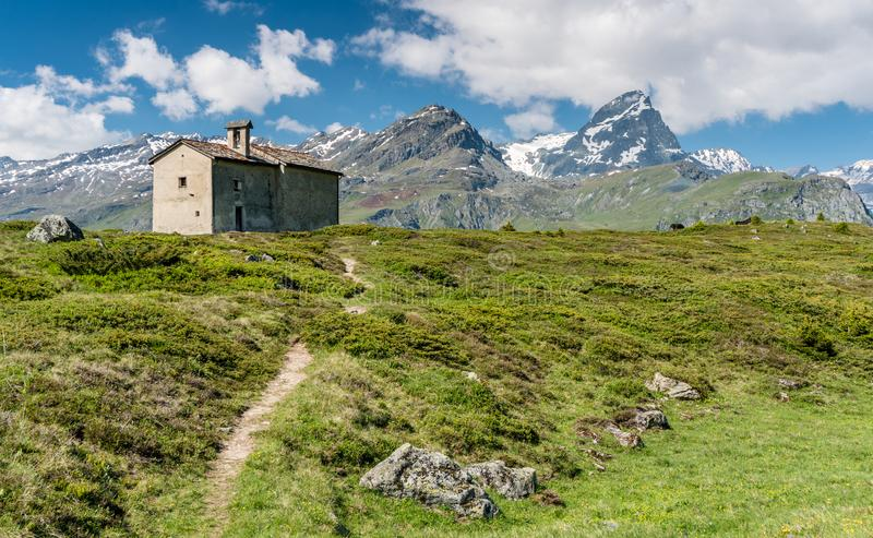 Mountain church in an idyllic mountain landscape in the summertime in the Alps with snow-capped peaks in the background. An mountain church in an idyllic stock photos