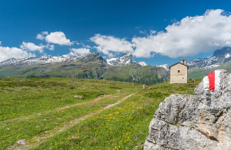 Mountain church in an idyllic mountain landscape in the summertime in the Alps with snow-capped peaks in the background and a hiki. A mountain church in an stock photo