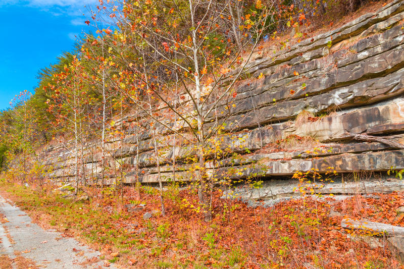 Mountain cliff with rock layers, colorful stone formations of rocks stacked over the hundreds of years. Autumn season. stock image