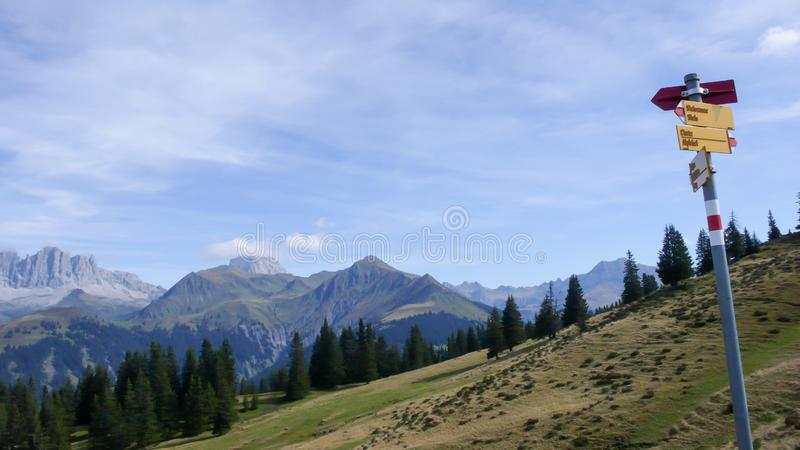 Mountain climber carrying a lot of climbing equipment in the Mischabel mountain range in the Swiss Alps above Saas green valley an royalty free stock photography
