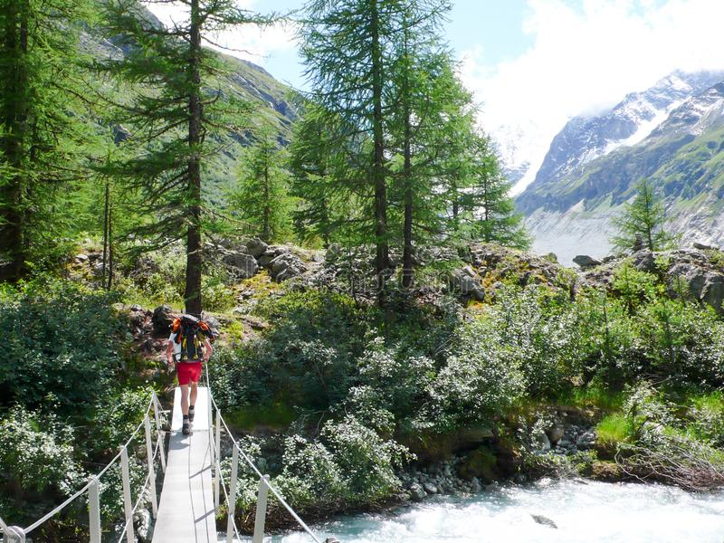 Mountain climber hikes over a wooden bridge and mountain river on his way to base camp in the Alps of Switzerland royalty free stock photo