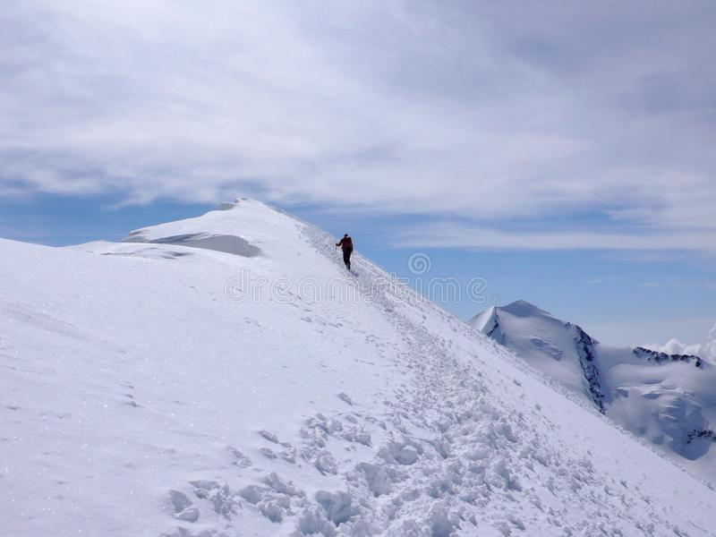 Mountain climber hiking along a long snow ridge on his way to a high alpine summit with tracks in the foreground. Mountain climber hiking along a long snow ridge royalty free stock images