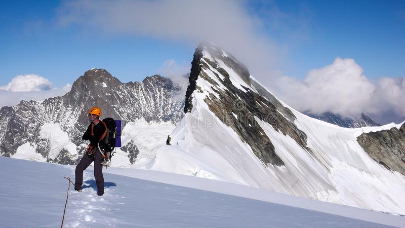 Mountain climber standing on a glacier and looking at the wonderful mountain landscape and panorama around him stock photos