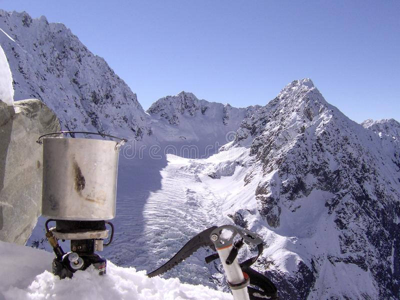 A mountain climber takes a break to cook food in the snow stock photo