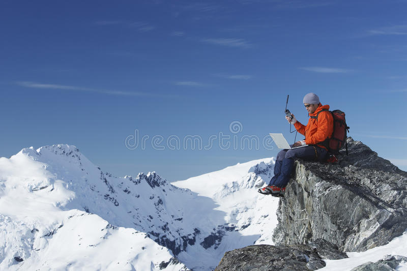 Mountain Climber Using Laptop And Walkie Talkie On Mountain Peak. Mountain climber using laptop with walkie talkie on mountain peak against blue sky royalty free stock photo