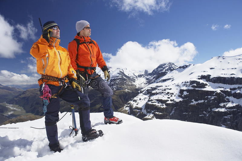 Mountain Climber Using Walkie Talkie By Friend On Snowy Peak. Two male mountain climbers on snowy peak against sky with one using walkie talkie stock photography
