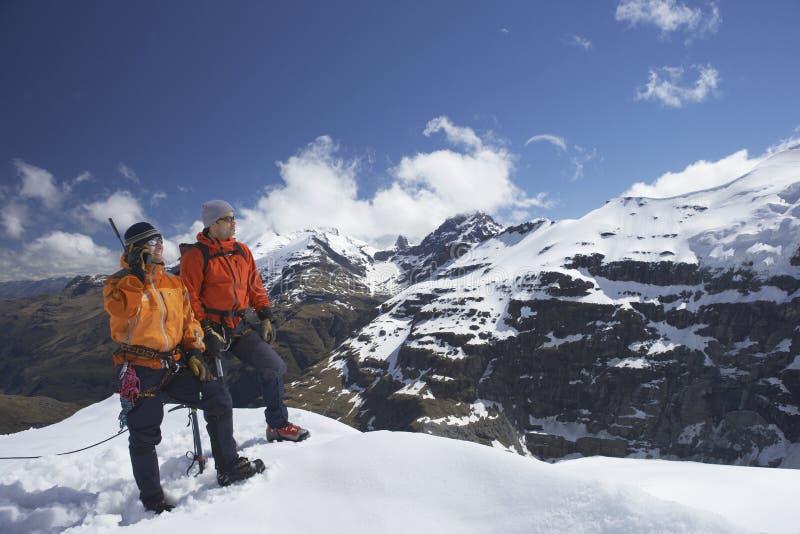 Mountain Climber Using Walkie Talkie By Friend On Snowy Peak. Two male mountain climbers on snowy peak against sky with one using walkie talkie royalty free stock photo