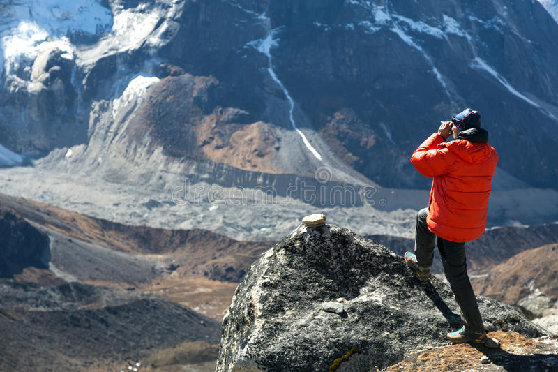Mountain Climber in warm Jacket taking Picture of Valley royalty free stock images
