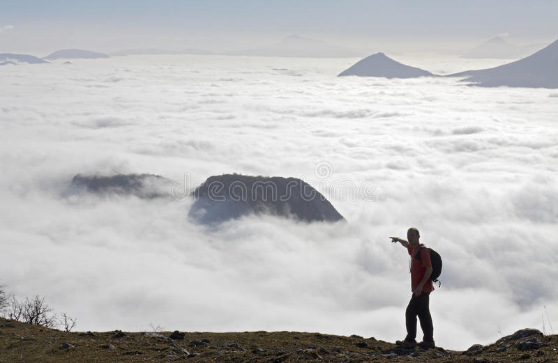 Mountain climber who looks over clouds royalty free stock images
