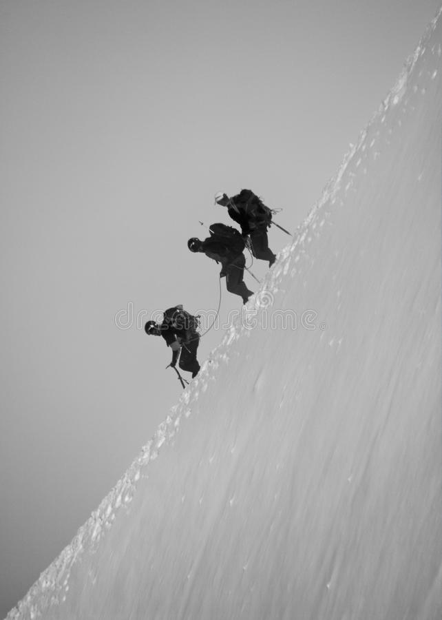 Mountain climbers. Three mountain climbers going down the steep slope in winter. Mont Blanc route stock image