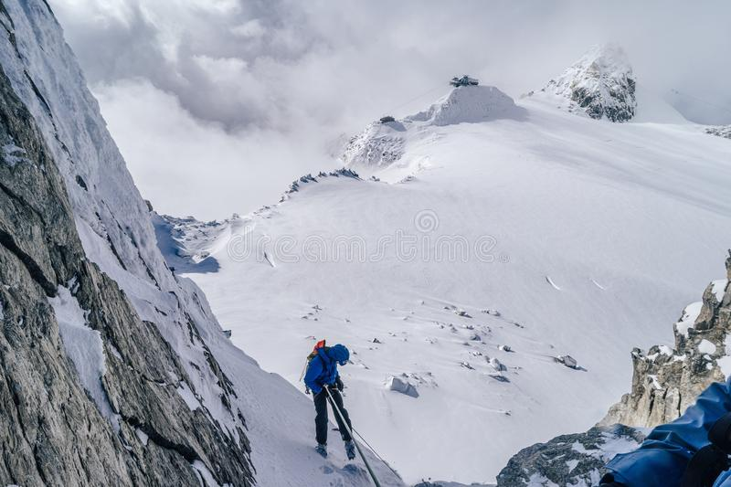 Mountain climbers climbing the snow covered Alps in Mont Blanc Massif. The mountain climbers climbing the snow covered Alps in Mont Blanc Massif stock photos