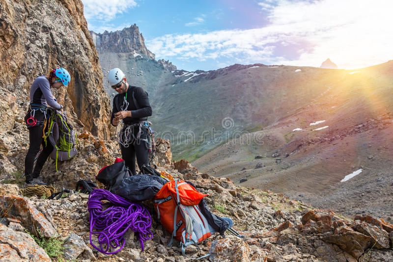 Mountain climbers preparing for ascent Sunshine Background stock image