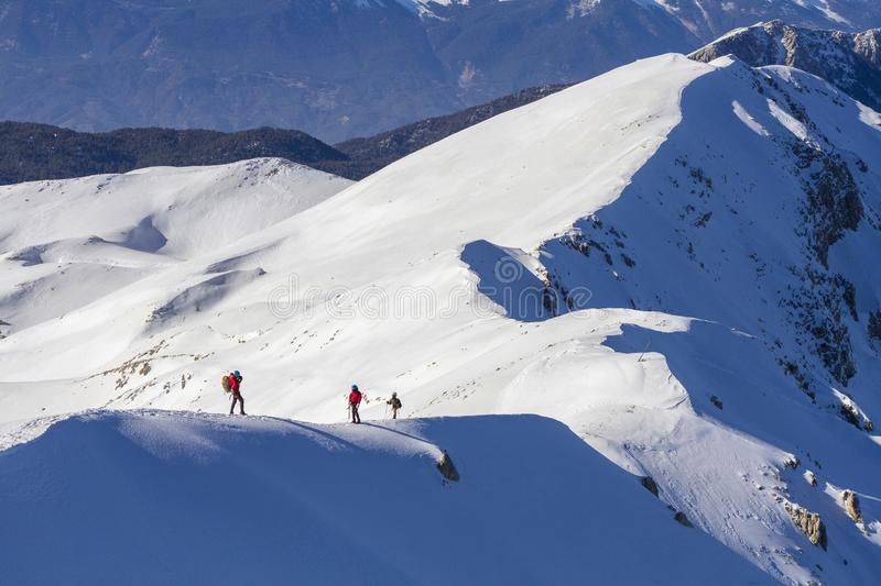 3 mountain climbers walk on snow in the mountains royalty free stock photography